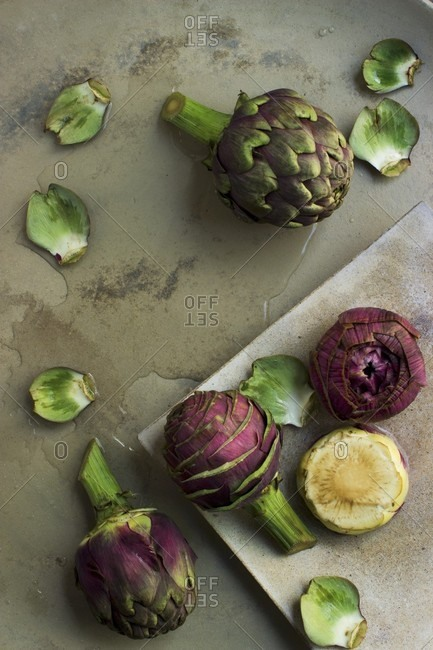 Whole artichokes, prepared artichokes and artichoke hearts on a stone platter