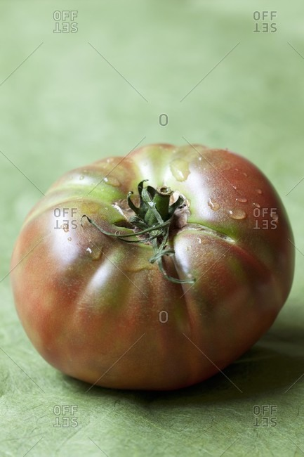 A tomato on a green surface