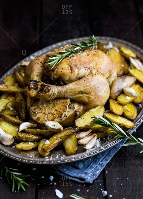 Roast chicken with garlic, potatoes and rosemary