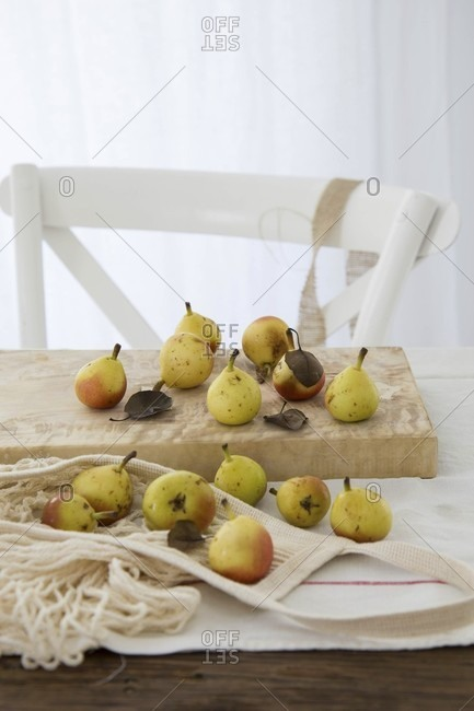 Small pears with leaves on a wooden chopping board