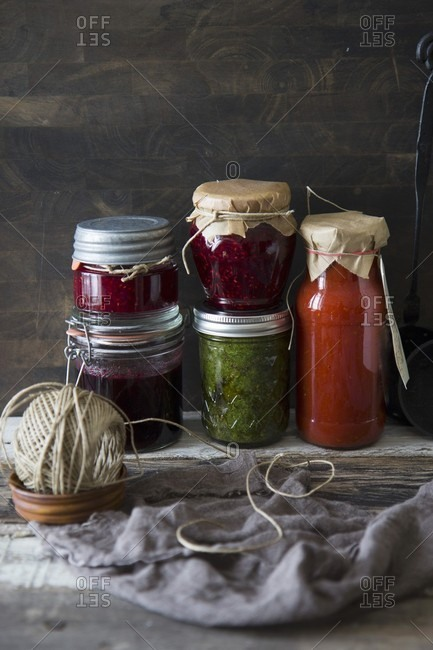 Homemade jams and sources against a rustic wooden wall