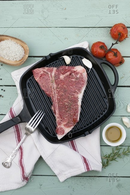 A raw T-Bone steak in a grill pan