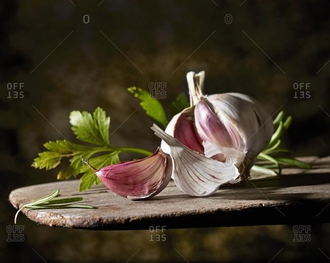 A garlic bulb and flat-leaf parsley on a wooden board