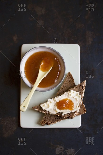 Medlar jam on a bowl and on a slice of toast with cream cheese (seen from above)