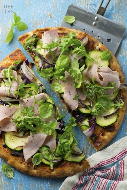 Pizza with courgette, rocket and ham, halved