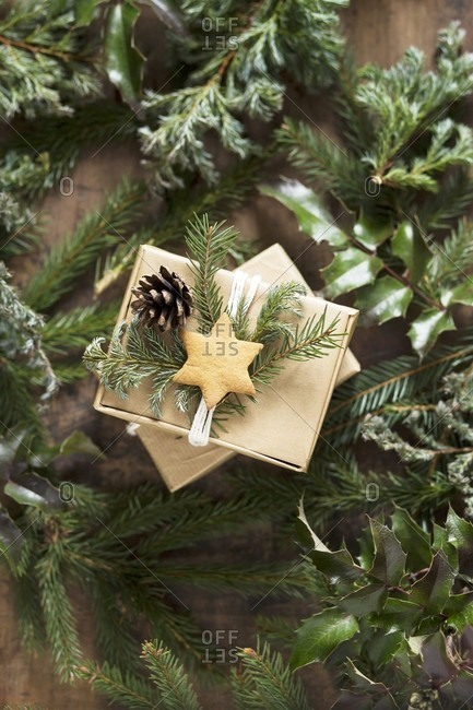 Gift boxes decorated with pine sprigs, pine cones and a star shaped biscuit