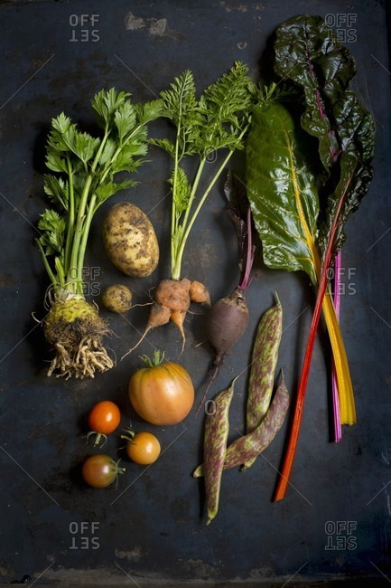 Various fresh vegetables on a dark surface (seen from above)