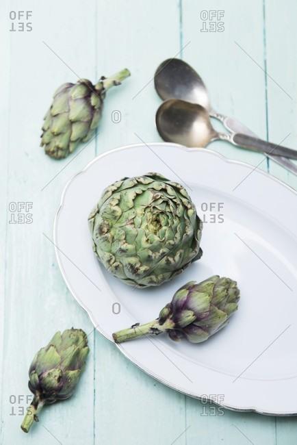 A fresh artichoke and baby artichokes on a porcelain platter