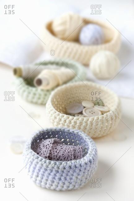 Pastel-coloured, crocheted baskets of haberdashery items