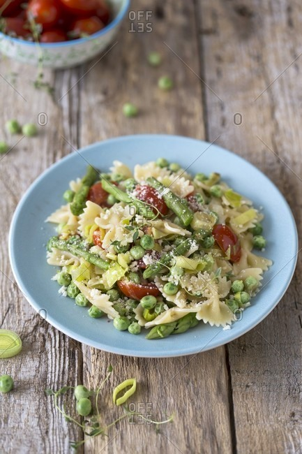 Pasta Primavera with asparagus, peas, leek and tomatoes on wooden surface