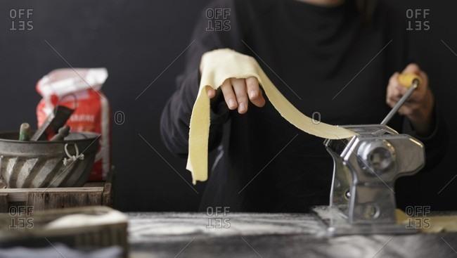 Fresh pasta dough being turned through a pasta machine