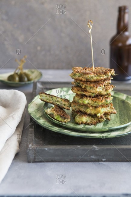 A stack of broccoli fritters with capers