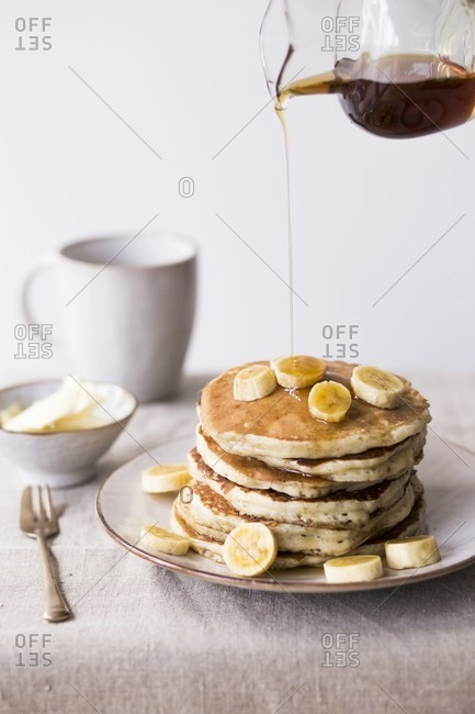 A stack of pancakes with bananas and maple syrup