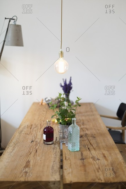 Pendant lamp above rustic dining table made from two old boards
