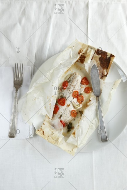 Fish with cherry tomatoes baking parchment paper