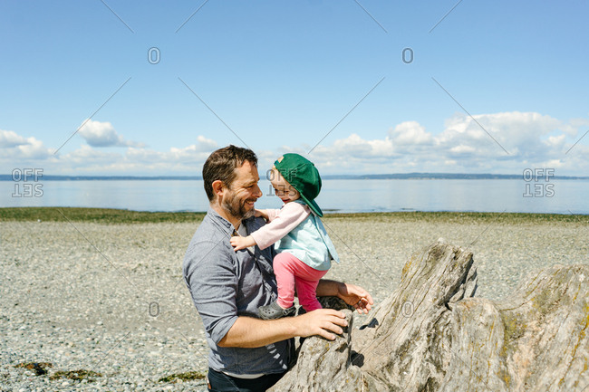 Father and baby playing on driftwood