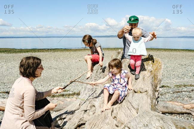 Family playing on driftwood in Carkeek Park, Seattle, Washington