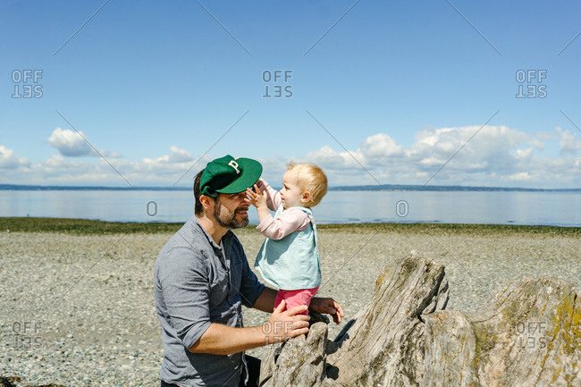 Baby reaching for dad's hat on driftwood