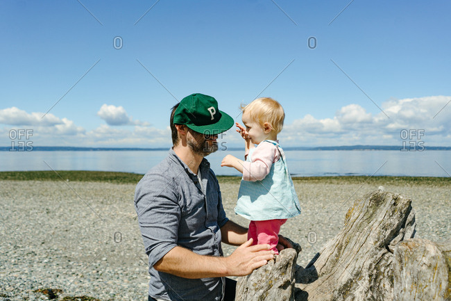 Baby girl reaching for dad's hat on driftwood