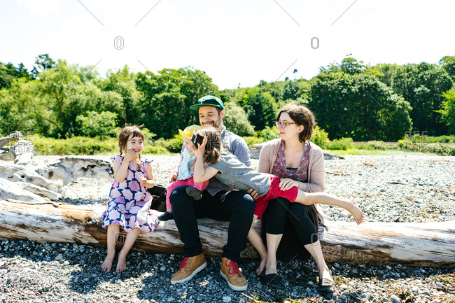 Family sitting together on driftwood in Carkeek Park, Seattle, Washington