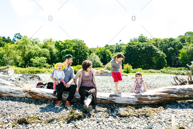 Family on a log on a beach in Seattle, Washington