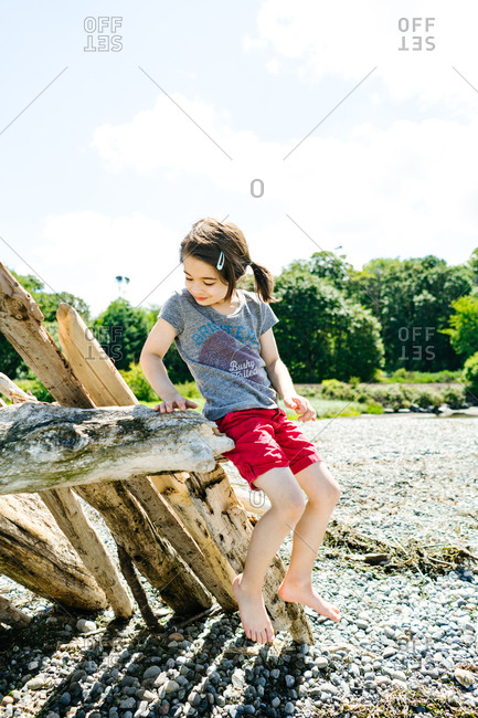 Little girl playing in driftwood fort on a beach