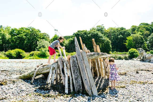 Sisters playing in driftwood fort on a beach
