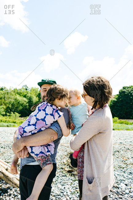 Girls kissing while parents hold them on a beach in Seattle, Washington