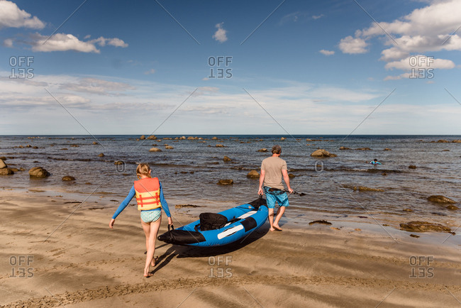 Father and daughter carrying kayak into water, New Zealand
