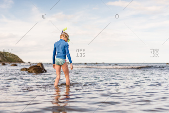 Girl exploring in waves on Hawke's Bay, New Zealand