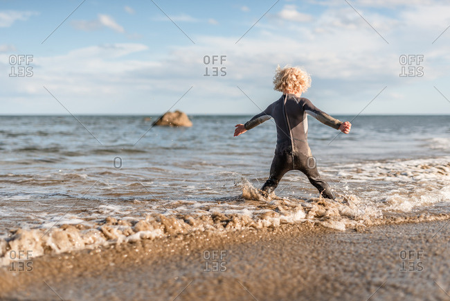 Rear view of little boy playing in waves on Hawke's Bay, New Zealand