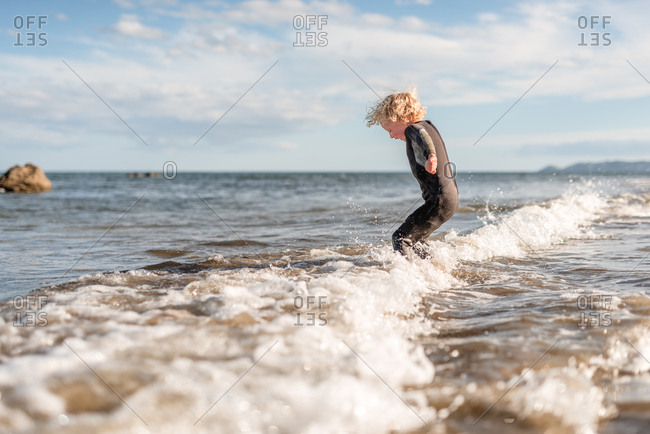 Side view of young boy jumping in waves on Hawke's Bay, New Zealand