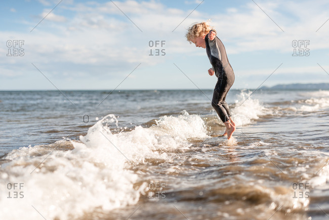 Side view of little boy jumping in waves on Hawke's Bay, New Zealand