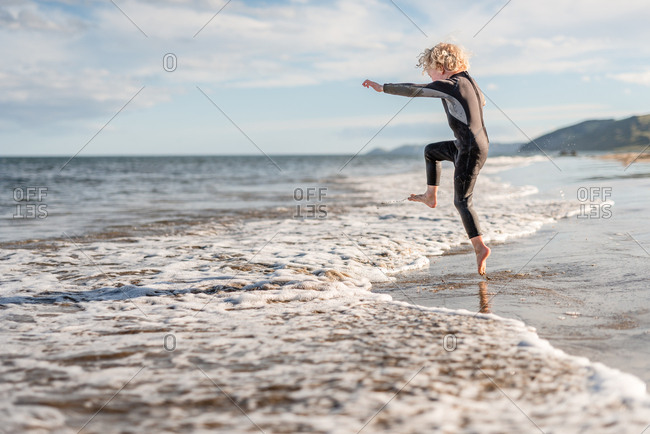 Young boy jumping in waves on Hawke's Bay, New Zealand
