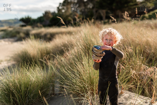 Boy gathering paua shells on Hawke's Bay, New Zealand