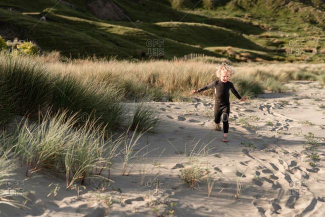 Boy running in sand on Hawke's Bay, New Zealand