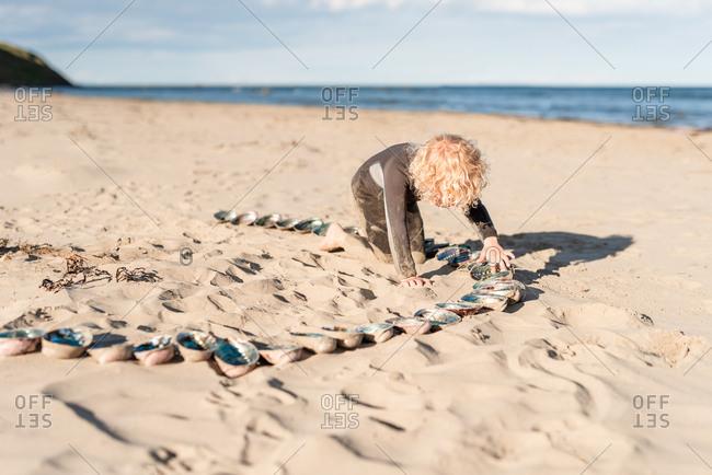 Boy arranging paua shells in the sand on Hawke's Bay, New Zealand
