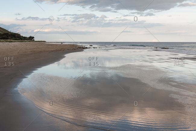 Cloudy sky reflecting in tide on Hawke's Bay, New Zealand