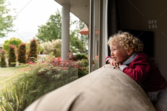 Boy sitting on back of couch looking out window