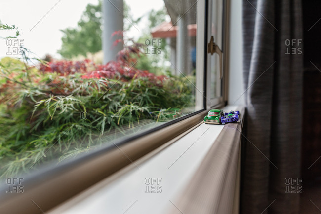 Toy cars sitting on windowsill