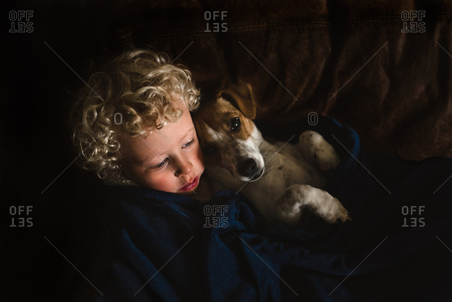 Boy wrapped in a blanket cuddling with his dog
