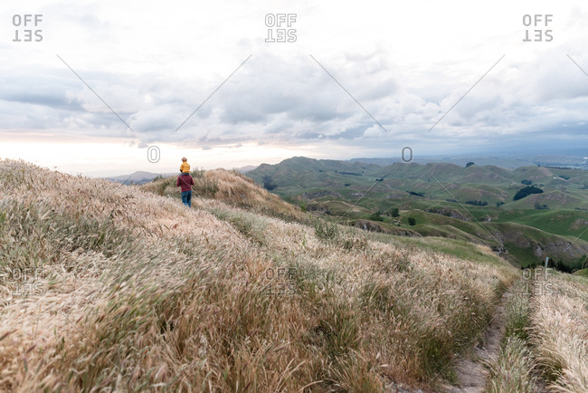 Father carrying son on his shoulders on Te Mata Peak in New Zealand