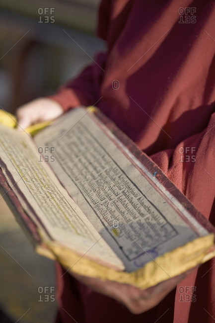 Monk holding Buddhist prayer book, Rumtek Gompa, Gangtok, Sikkim, India, Asia