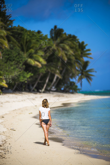Woman walking along a tropical beach, Rarotonga Island, Cook Islands, South Pacific, Pacific