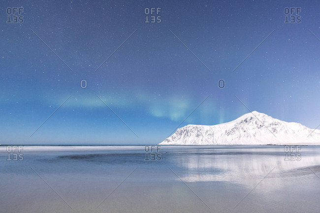 Northern Lights (Aurora borealis) on the snowy peaks reflected in the sea, Skagsanden beach, Flakstad, Nordland county, Lofoten Islands, Norway, Scandinavia, Europe