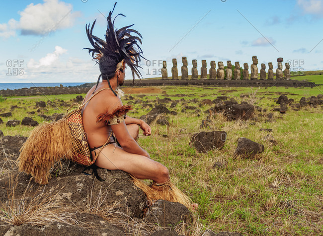 Native Rapa Nui man in tradititional costume and Moais in Ahu Tongariki, Rapa Nui National Park, UNESCO World Heritage Site, Easter Island, Chile, South America