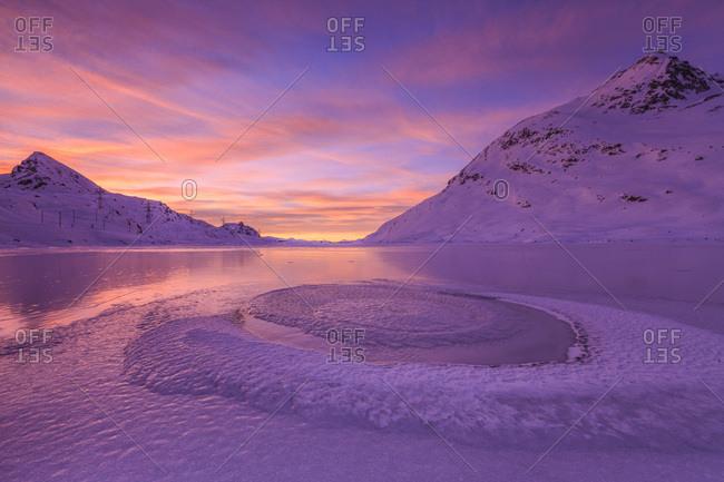 Frost creating unusual shapes in the middle of Lake Bianco at Bernina illuminated by the light of sunrise, Graubunden, Swiss Alps, Switzerland, Europe