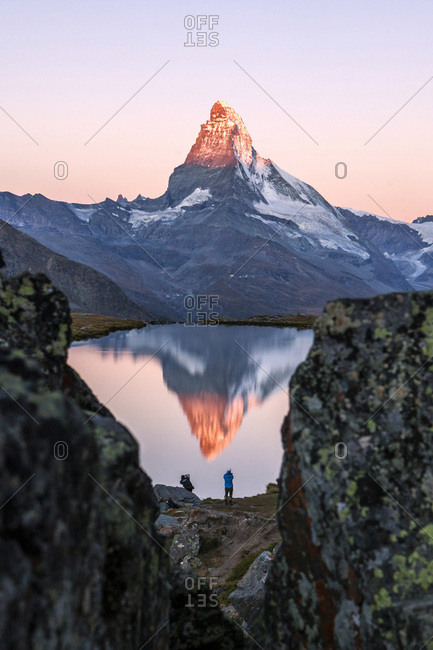 Hikers admire the Matterhorn reflected in the Stellisee at sunrise, Zermatt, Canton of Valais, Pennine Alps, Swiss Alps, Switzerland, Europe