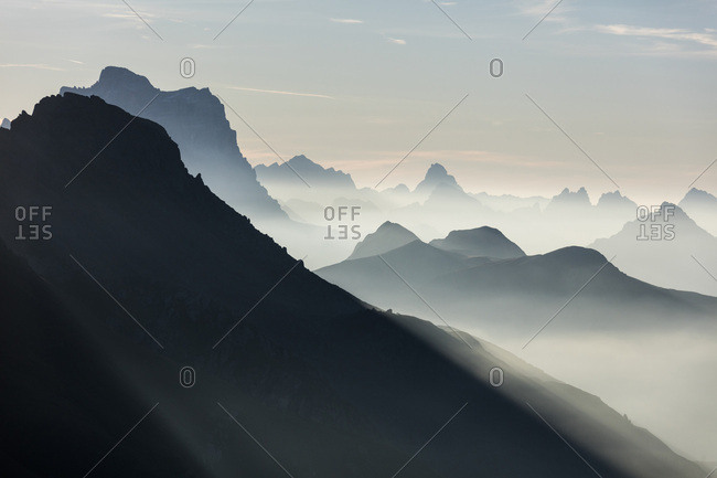Mist on peaks of Dolomites and Monte Pelmo seen from Cima Belvedere at dawn, Val di Fassa, Trentino-Alto Adige, Italy, Europe
