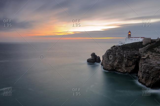 Dusk lights up the lighthouse overlooking the Atlantic Ocean, Cabo De Sao Vicente, Sagres, Algarve, Portugal, Europe